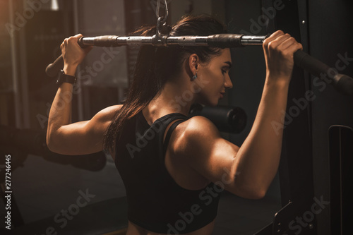 Photo sur Toile Fitness Young fit athletic girl having workout in gym. Brunette beautiful healthy female indoor training.