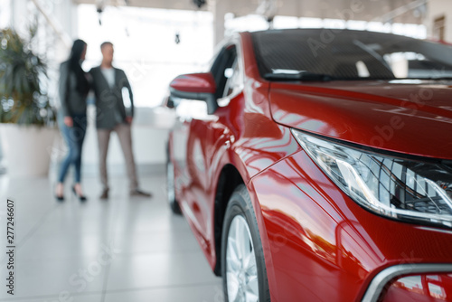 Photographie Couple buying new red car in showroom