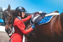 Girl Rider Adjusts Saddle On H...