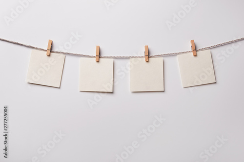 Fotografie, Obraz  Four old paper blank notes hanging on the rope with wooden clothespins on white