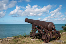 Old Antique Cannon At Fort James On The Edge Of A Cliff With Lots Of Clouds In The Sky, Antigua