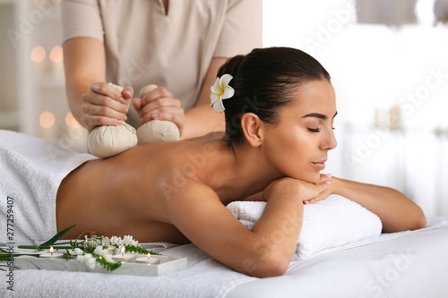 Stampa su Tela  Beautiful young woman receiving massage in spa salon