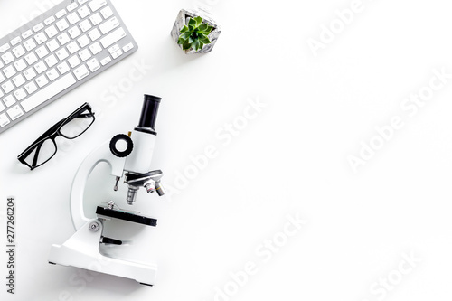 Photo  Laboratory desk with keyboard and microscope on white background top view space