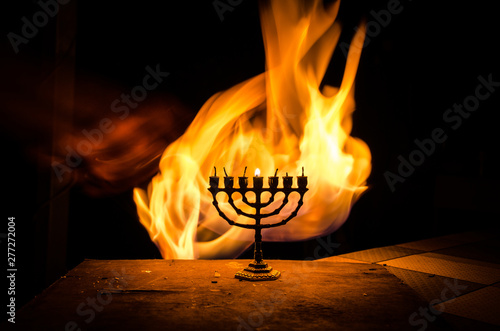 Fototapeta Low key image of jewish holiday Hanukkah background with menorah on dark toned f