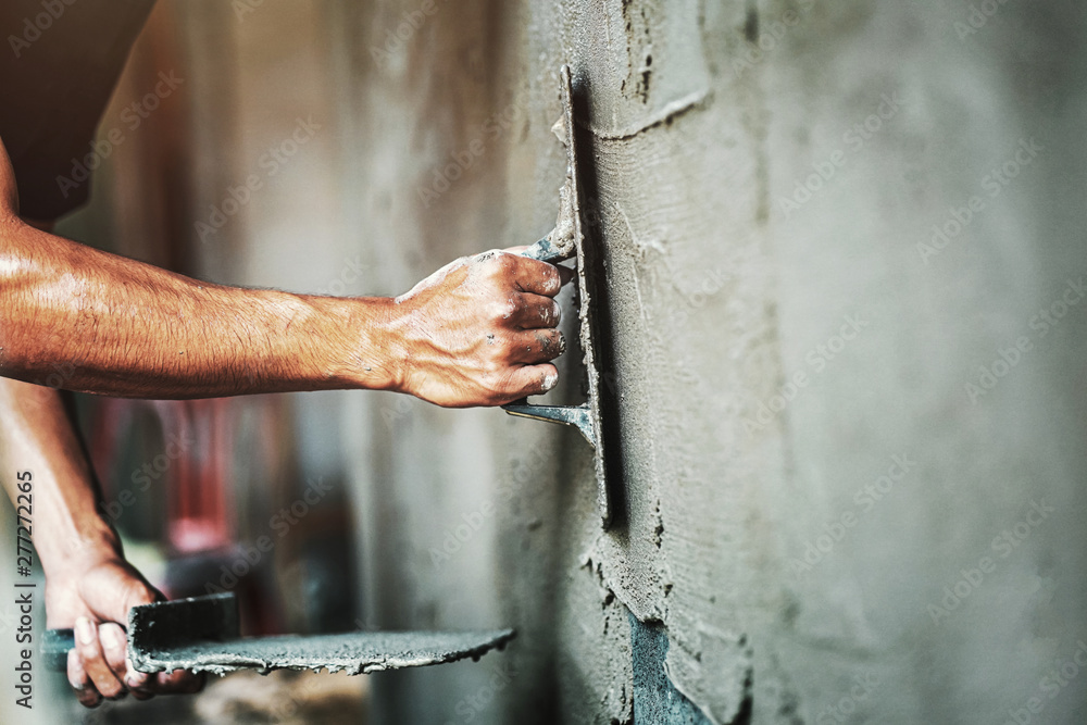 Fototapeta closeup hand of worker plastering cement at wall for building house
