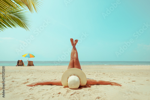 Leisure in summer - Young woman in straw hat lying sunbathe on a tropical beach Wallpaper Mural