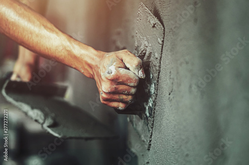 Fototapeta closeup hand of worker plastering cement at wall for building house obraz na płótnie