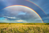 Fototapeta Tęcza - Rainbow over stormy sky. Rural landscape with rainbow over dark stormy sky in a countryside at summer day.