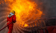 Brave Firefighter Using Extinguisher And Water From Hose For Fire Fighting, Firefighter Spraying High Pressure Water To Fire, Firefighter Training With Dangerous Flames, Copy Space-Image