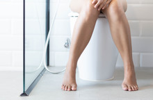 Closeup Woman Sitting On Toilet In The Morning, Selective Focus
