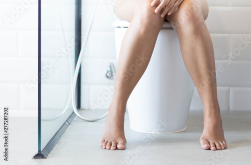 Pinturas sobre lienzo  Closeup woman sitting on toilet in the morning, selective focus