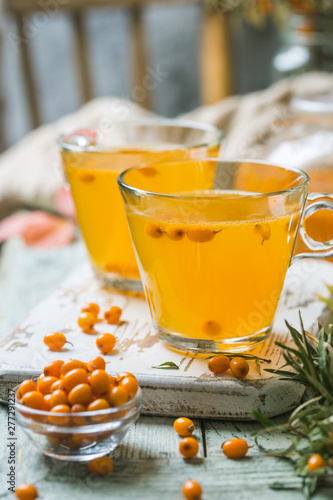 Vitaminic healthy sea buckthorn tea in a glass cups with fresh raw sea buckthorn berries on a white wooden rustic background