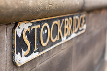 Weathered Street Sign For The Stockbridge Neighborhood With Golden Letters