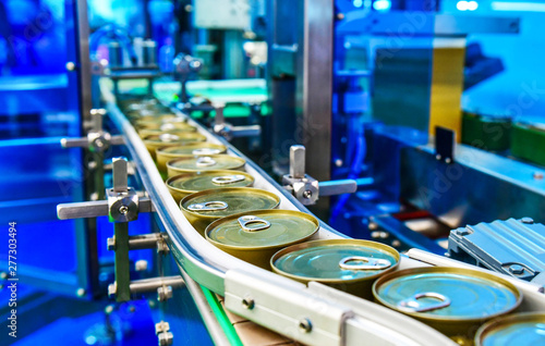 Fotografiet  Canned food products on conveyor belt in distribution warehouse