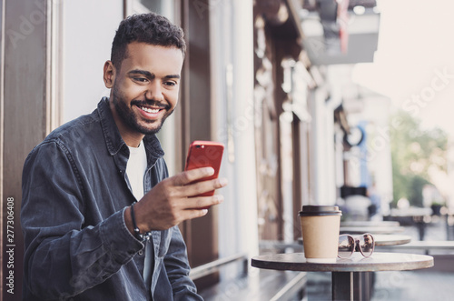 Handsome man using smartphone in a city. Young handsome student men having coffee break and texting on his mobile phone. Modern lifestyle, city life concept - 277306408