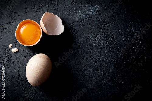 Photo Organic chicken eggs on dark wooden background with copy space.
