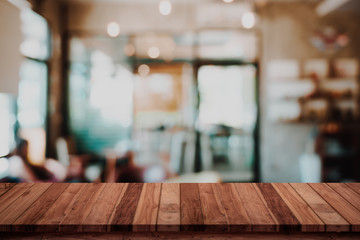 Empty wood table with blur cafe or coffee shop background.