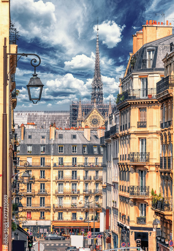 Latin Quarter street view of Paris, France. Blue sky, buildings and traffic. Shot in april daylight with Notre Dame in the background. - 277310669