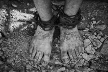 Close-up Shot Of Barefoot Legs Tied Up With Old Chain