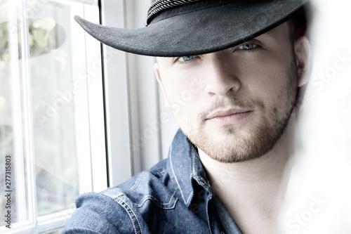 Fotografía  Portrait of handsome cowboy wearing hat sitting in window