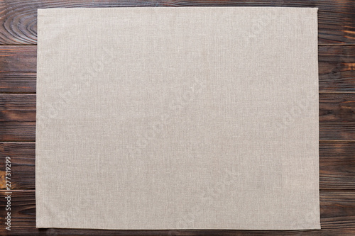 gray cloth napkin on rustic dark wooden background top view with copy space Fototapeta