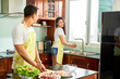 Young Asian couple wearing aprons standing at domestic kitchen and preparing food for dinner together