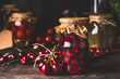 Cherry fruit compote in glass jars on dark rustic kitchen table. Close up. Preserved organic food from garden. Canning and conservation of harvest. Healthy homemade food