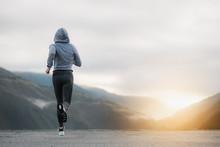 Shot Of A Beautiful Adult Woman Running At Sunrise.