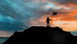 Leinwanddruck Bild - business, success, leadership, achievement and people concept - silhouette of businessman with flag on mountain top over sunset background