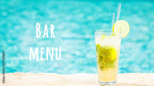 Mojito cocktail at the edge of a resort pool. Concept of luxury vacation. Outdoor pool background. Horizontal, wide screen format. Bar menu wording