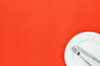 canvas print picture - Fork and knife on white round ceramic plate on orange background with copy space. Top down view.