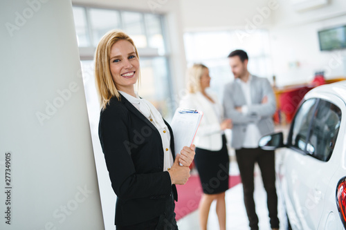 Photographie Professional salesperson selling cars at dealership to buyer