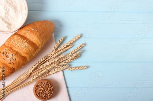 bread and wheat spikelets on wooden background top view.
