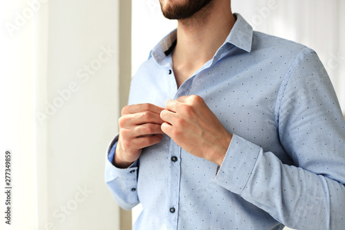 Carta da parati Man buttons sleeves on blue linen dress shirt in bedroom at slight angle