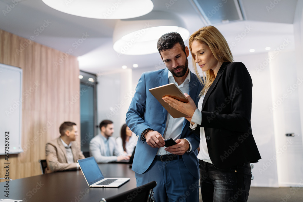 Fototapeta Businesspeople discussing while using digital tablet in office
