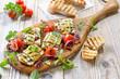 Leinwandbild Motiv Vegetarisch grillen: Leckere griechische Feta-Zucchini-Päckchen  mit Zwiebeln und Kräutern sowie  Grilltomaten – Grilled Greek feta cheese wrapped in thin zucchini slices and onions