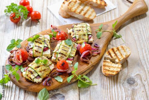 Fototapeta Vegetarisch grillen: Leckere griechische Feta-Zucchini-Päckchen  mit Zwiebeln und Kräutern sowie  Grilltomaten – Grilled Greek feta cheese wrapped in thin zucchini slices and onions obraz