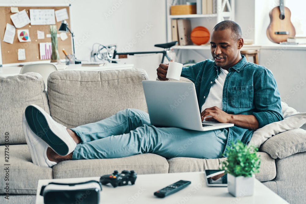 Fototapety, obrazy: Happy to rest. Handsome young African man using laptop and smiling while sitting indoors