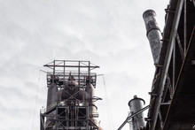 Upward View Of Blast Furnaces In An Old Steel Manufacturing Plant Against Gray Sky, Horizontal Aspect