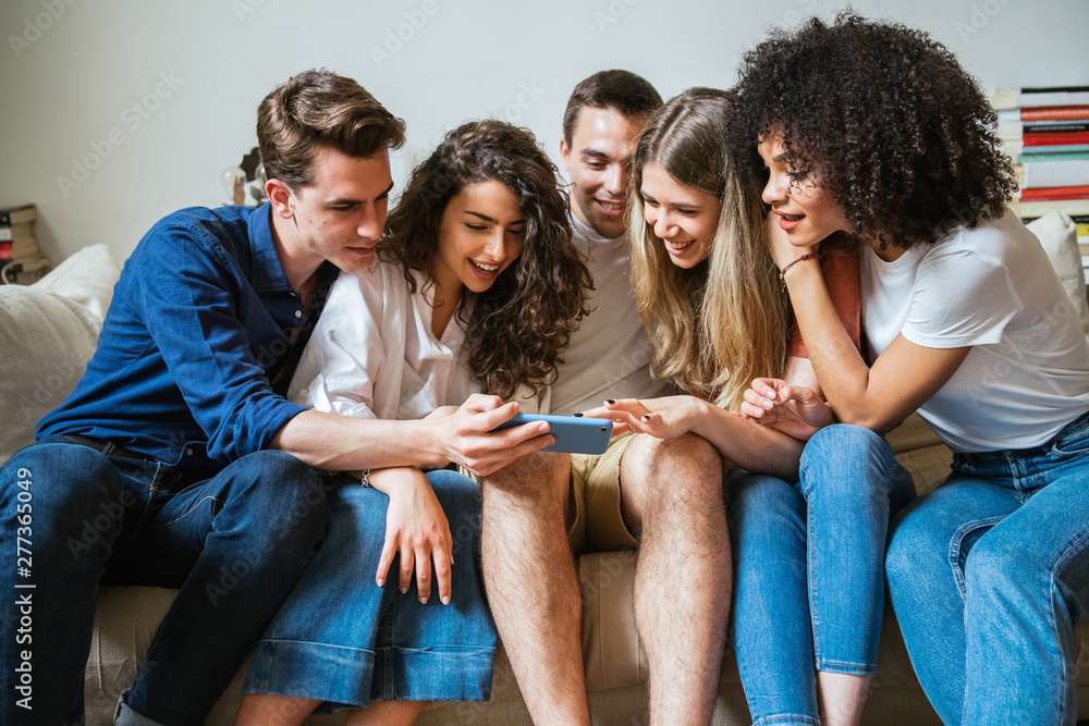 Fototapeta Group of friends sitting on the sofa at home watching a woman's smart phone - Millennials have fun together in an apartment