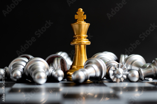 Fotografía Gold king chess piece win over lying down silver pawn on black background