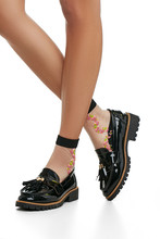 Cropped Side Shot Of Girl's Legs Wearing Black Nylon Socks, Adorned With Orange Floral Insertion. The Lady Is Wearing Patent Leather Shoes With Ribbed Soles And Tassels, Posing On White Background.