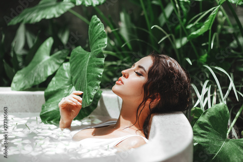 Canvas Print Woman relaxing in round outdoor bath with tropical flowers, organic skin care, l