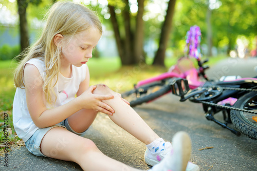 Cute little girl sitting on the ground after falling off her bike at summer park Canvas Print
