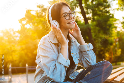Pleased happy young teenage girl student sitting outdoors in beautiful green park listening music with headphones. - 277374297