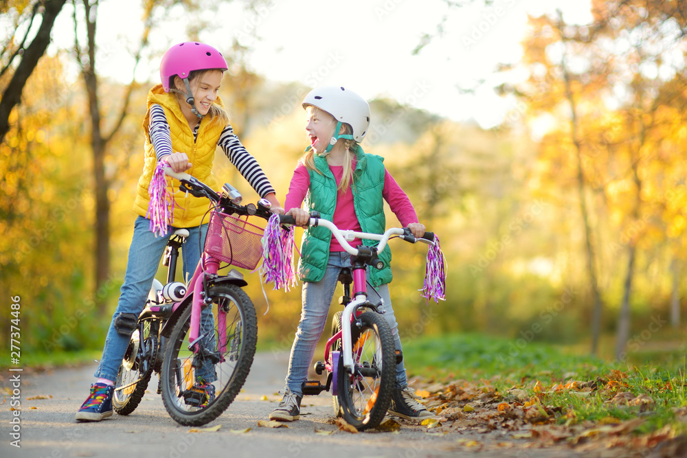 Fototapety, obrazy: Cute little sisters riding bikes in a city park on sunny autumn day. Active family leisure with kids.