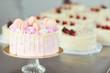 Leinwandbild Motiv Pink cake decorated with macaroons on the table.