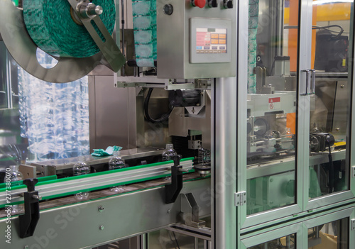 Process of PET plastic bottle on automatic sleeve labeling machine Tablou Canvas