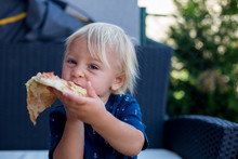 Cute Little Caucasian Kid Eating Pizza. Hungry Child Taking A Bite From Pizza On A Pizza Party, Outdoors