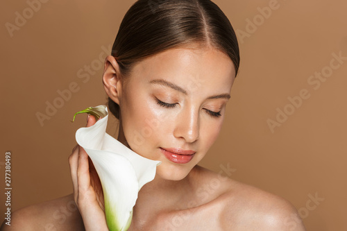 Image of calm half-naked woman holding white flower with closed eyes